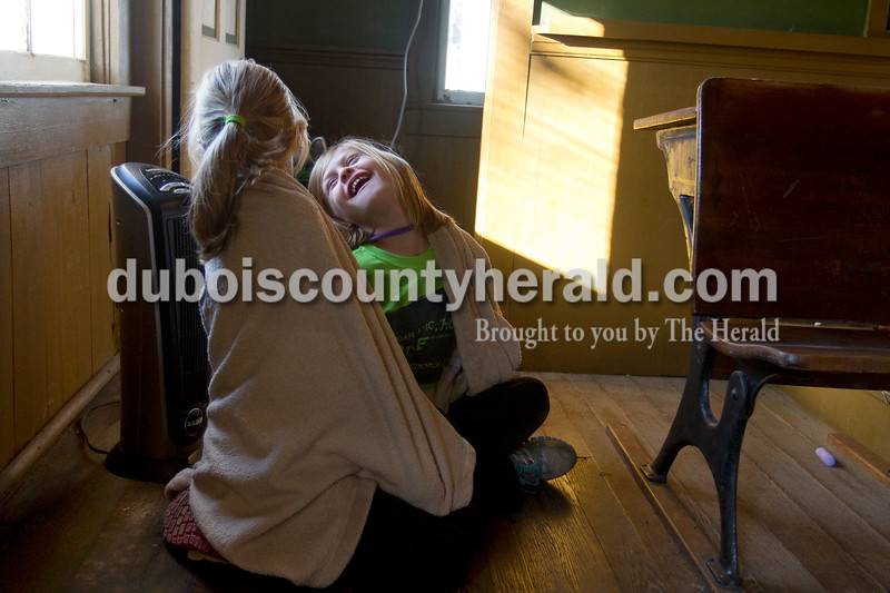 Olivia Corya/The Herald<br /> Maddux Marshall of Huntingburg, 6, warmed herself with a space heater as she and her cousin Grace Meece of Huntingburg, 11, shared a blanket inside a school house behind Zoar United Methodist Church in Holland on Saturday. Earlier that day, both girls participated in a kids' bike-a-thon that was part of the final event in a series of fundraisers for the Lange-Fuhs Cancer Center Patient Emergency Fund. The girls were waiting for two speakers to talk about the impact cancer has on so many people's lives.