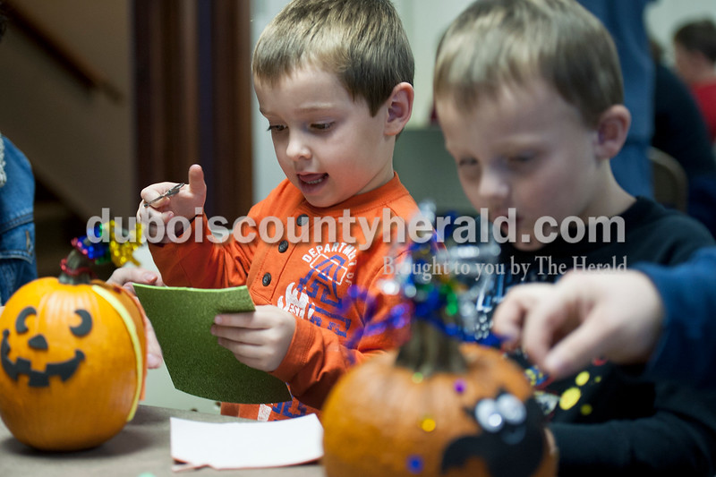 "Olivia Corya/The Herald<br /> Breckin Jochem of Huntingburg, 4, cut shapes out of sparkly foam next to his friend Aiden Stahl of Huntingburg, 4, as they participated in a pumpkin decorating party at the Huntingburg Public Library on Saturday. Breckin said he was decorating his pumpkin to be ""a happy face,"" and Aiden said his would be transformed into a  ""birthday pumpkin."""