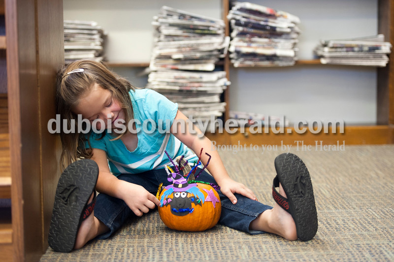 "Olivia Corya/The Herald<br /> Reece Jo Tretter of Huntingburg, 7, looked at the pumpkin she just created during a pumpkin decorating party at the Huntingburg Public Library as she waited for her mom to take her home on Saturday. She said she chose a ""sparkly bat/witch"" design because ""If there's something to do with sparkles I will do it."""