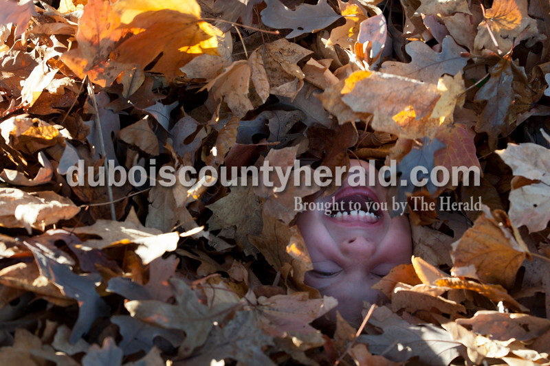 Olivia Corya/The Herald<br /> Maddux Marshall of Huntingburg, 6, laughed as her cousins buried her in leaves outside Zoar United Methodist Church in Holland on Saturday. They were waiting for bikers to finish a bike-a-thon organized by the church that was the final event in a series of fundraisers for the Lange-Fuhs Cancer Center Patient Emergency Fund. Maddux rode in the kids' bike-a-thon earlier that day.