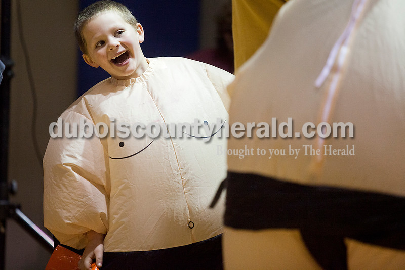 Rachel Mummey/The Herald<br /> Gavin Schlachter of Birdseye, 5, playfully darted out from around his mother, Holly, while pretend sumo wrestling with his brother Alex, 8, at the Ruxer Student Center on the Vincennes University Jasper Campus during the fright night and trunk-or-treat event hosted by the Campus Activity Board and the Student Government Association Friday. The event, which was moved indoors because of inclement weather, still saw a variety of faces and costumes.