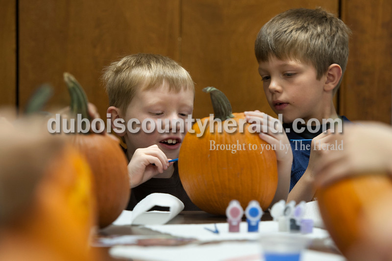 "Olivia Corya/The Herald<br /> Friends Parker Rehms, left, and Owen Morrison, both of Huntingburg, 7, checked on each other's progress during a pumpkin decorating party at the Huntingburg Public Library on Saturday. Parker chose to paint a ""Dracula with diamonds,"" and Owen created a ""half water, half fire snake"" design."