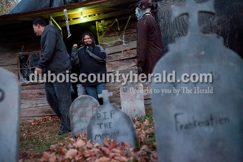 Still laughing from a good scare, Oscar and Maria Dubon of Huntingburg exited into the cemetery after walking through Barry and Jennifer Kline's haunted pirate ship on N. Sycamore St. on Halloween.
