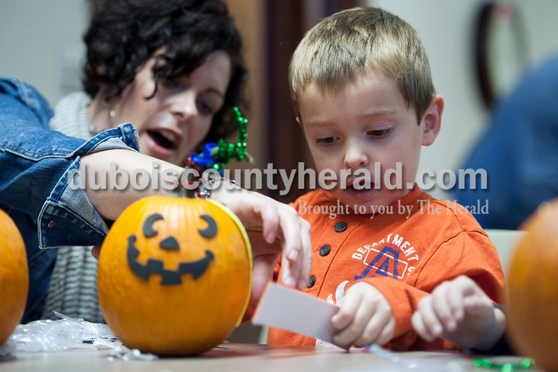 "Olivia Corya/The Herald<br /> Breckin Jochem of Huntingburg, 4, peeled the sticky backing off sparkly foam with the help of his mom Mara during a pumpkin decorating party at the Huntingburg Public Library on Saturday. Breckin said he was decorating his pumpkin to be ""a happy face."""