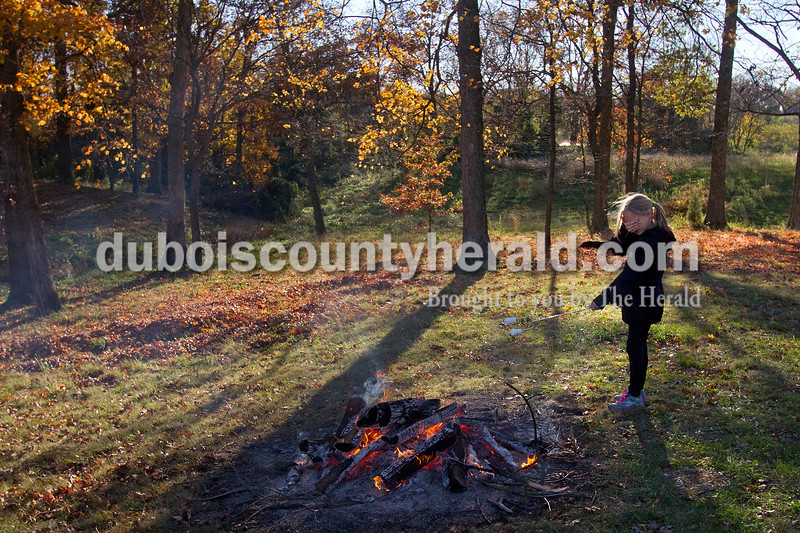 Olivia Corya/The Herald<br /> Grace Meece of Huntingburg, 11, shielded her face from smoke as she toasted marshmallows outside Zoar United Methodist Church in Holland on Saturday. Earlier that day, she participated in a kids' bike-a-thon that was part of the final event in a series of fundraisers for the Lange-Fuhs Cancer Center Patient Emergency Fund. She also joined in for the ten mile adult bike-a-thon in addition to running a 5K just a few hours before.