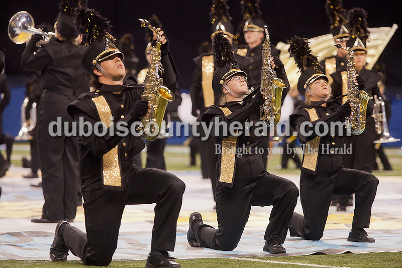 Jasper alto saxophonists sophomore Max Bradley, freshman Alyssa Sendelwick and sophomore Reagan Mooreman lifted their instruments during their performance at the Indiana State School Music Association State Marching Band Finals in Indianapolis Saturday