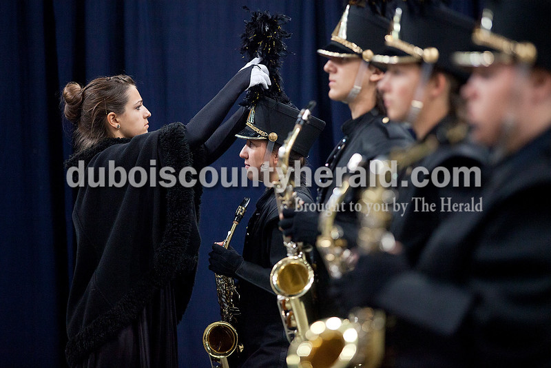Jasper junior Olivia June adjusted ___'s plume as she walked inspecting the bands uniforms for even the smallest flaws at the Indiana State School Music Association State Marching Band Finals in Indianapolis Saturday.
