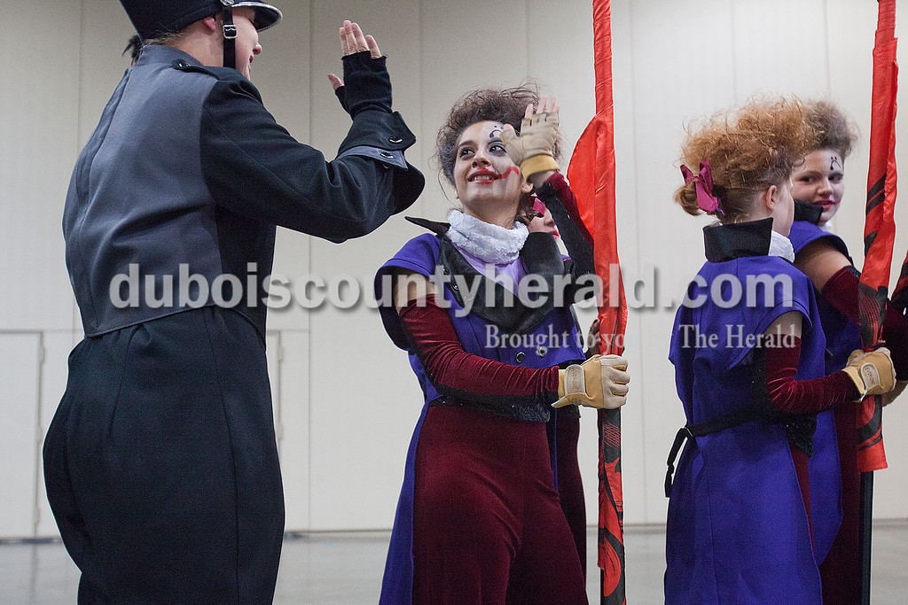 Southridge color guard Emily Calderon high-fived a member of the marching band as they lined up in preparation to perform at the Indiana State School Music Association State Marching Band Finals in Indianapolis Saturday.