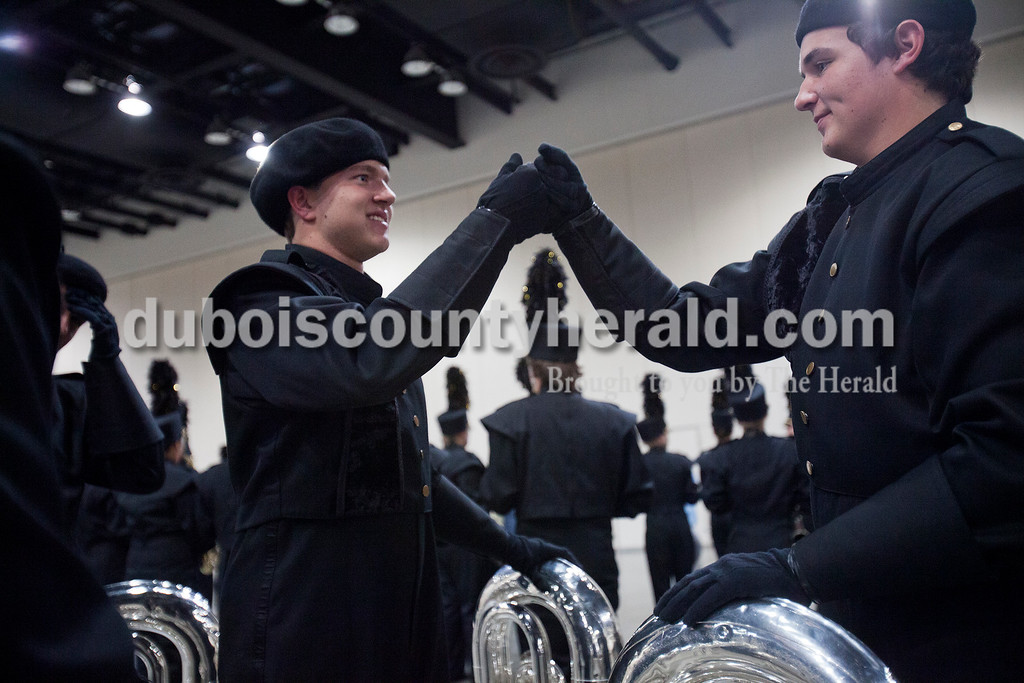Jasper senior Kyle Fischer and junior Nick Montee bumped fists at the Indiana State School Music Association State Marching Band Finals in Indianapolis Saturday.