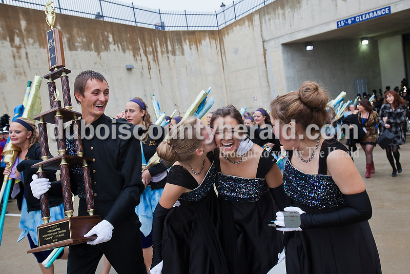 Jasper drum majors senior Zach Grewe carried the Marching Wildcats' first place trophy as junior Avery Charron planted a big kiss on junior Olivia June with junior Courtney Hayden as they celebrated their State Championship victory at the Indiana State School Music Association State Marching Band Finals in Indianapolis Saturday