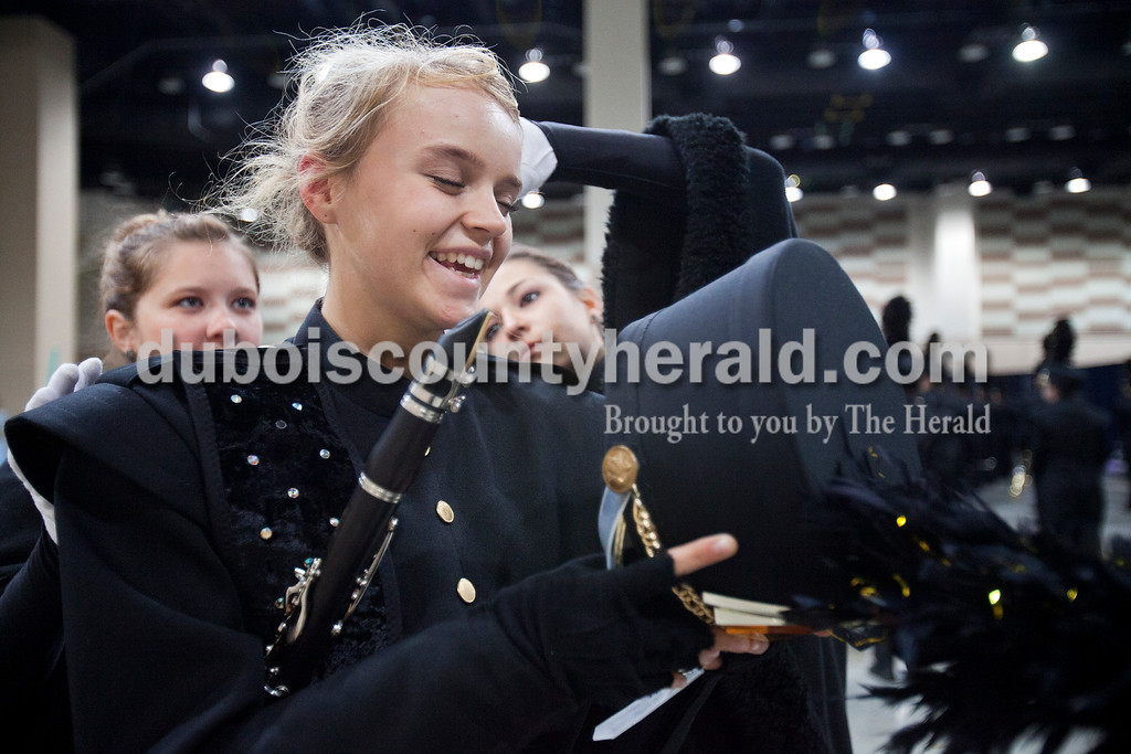 Jasper sophomore Maddi Roblin laughed as drum majors Courtney Hayden, left, and Olivia June, right, both juniors, tried pinning her hair up to go underneath her marching band hat at the Indiana State School Music Association State Marching Band Finals in Indianapolis Saturday.