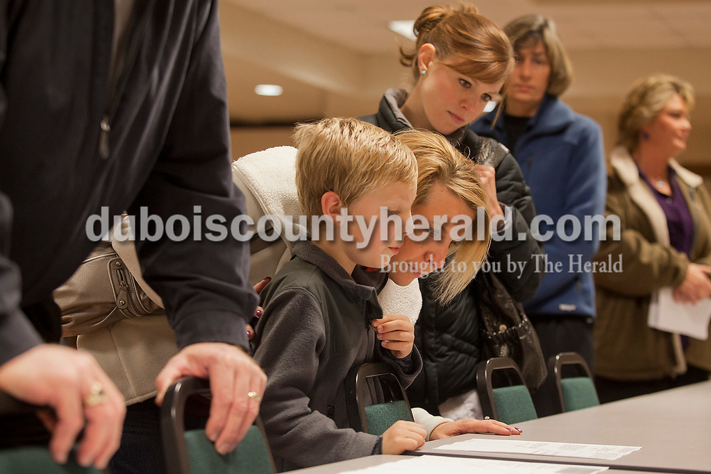Rachel Mummey/The Herald<br /> Michelle Bonner of Jasper leaned down to listen to her son, Julian, 7, ask her a question as they read the ballot issues while in line to vote next to Kendra Rottet and Kathy McClain, both of Jasper, at the Habig Community Center in Jasper on Tuesday.