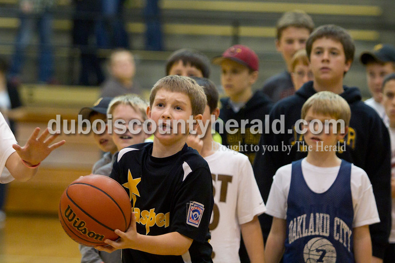 Olivia Corya/The Herald<br /> Grant Ahlbrand of Jasper, 11, prepared to take aim during a kids only game of knockout after the Jasper versus Southridge girls basketball match at Cabby O'Neill Gymnasium on Saturday night. The Wildcats defeated the Raiders 44-28.
