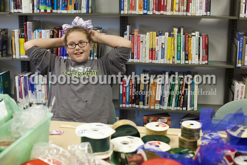 Rachel Mummey/The Herald<br /> Arika Deich of Birdseye, 10, found the perfect spot for her newly made bow as she attached the bow to her ponytail at the Birdseye Library on Tuesday. Local florist Margie Cooper of Birdseye was on hand to give demonstrations on how to make holiday bows and will be there next Tuesday evening from 4:30-6:30.