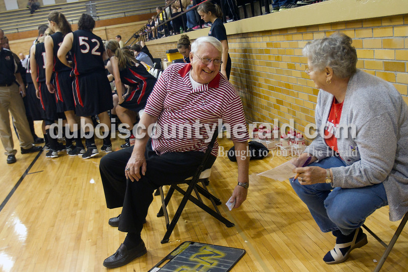 Olivia Corya/The Herald<br /> Don Astrike of Huntingburg, who has driven the Raiders to their games for 28 years, spoke to his wife Margie during a timeout in Saturday night's Jasper versus Southridge girls basketball game at Cabby O'Neill Gymnasium. The Wildcats defeated the Raiders 44-28.
