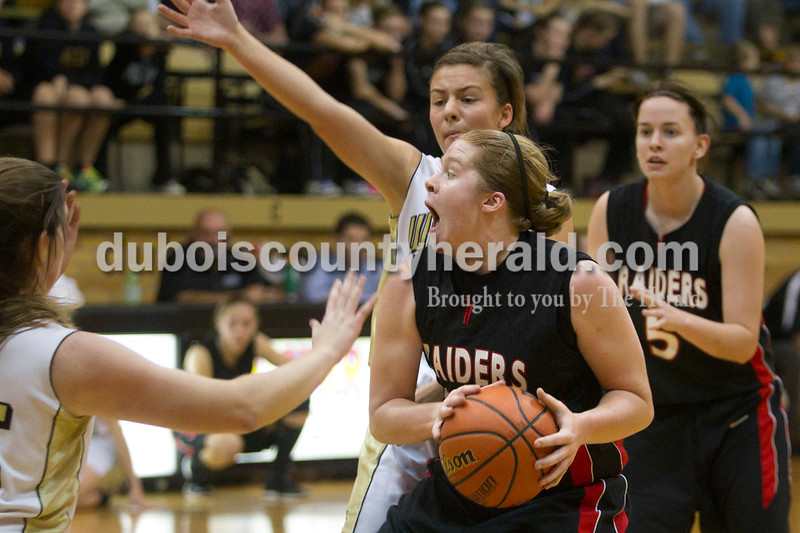 Olivia Corya/The Herald<br /> Southridge's Victoria Schaefer looked to pass as she was defended by Jasper's Emily Jones, behind Victoria, during Saturday night's game at Cabby O'Neill Gymnasium. The Wildcats defeated the Raiders 44-28.