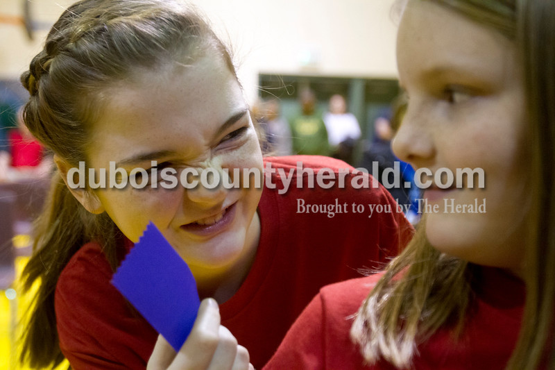 Olivia Corya/The Herald<br /> Huntingburg Elementary School student Evalyn Scherer, left, giggled with fellow fifth grader and spell bowl teammate Audra Hochgesang about their ribbons, which Evalyn thought smelled funny, during the Indiana Academic Spell Bowl Elementary Division at Ireland Elementary School on Thursday night.