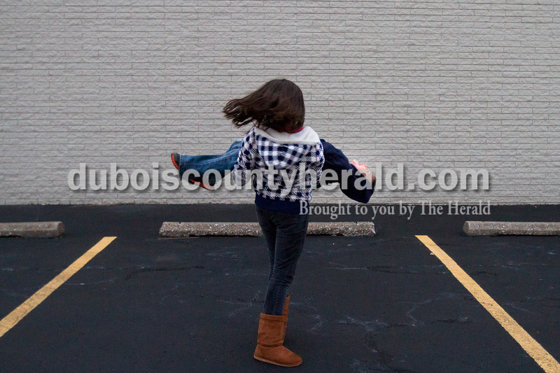 Olivia Corya/The Herald<br /> Susan Rodriguez of Jasper, 10, twirled her step brother Cruz Chavez, 7, in the parking lot of Ozanam Hall on the St. Vincent DePaul campus in Jasper while they waited to have dinner there with their family on Wednesday evening.