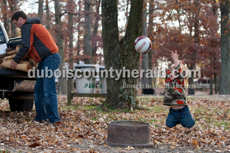 Olivia Corya/The Herald<br /> Brandon Buse of Huntingburg, 2, entertained himself with a basketball as his father Mark Buse, second from left, unloaded firewood with Joe Mullins of Haysville, another camper who offered to help, at the Dubois County Park on Friday. Along with his dad, Brandon was joined by his mom Stephanie and sister Blair for a weekend camping trip. The Buses just bought a camper last month, and this was their first time camping at this particular park. <br /> , where they were camping with their parents,