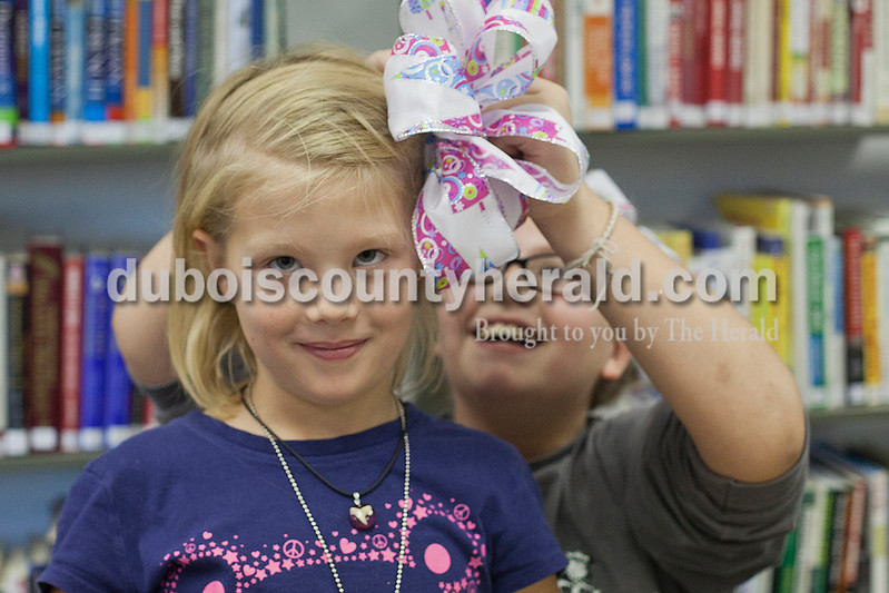 Rachel Mummey/The Herald<br /> Arin Deich of Birdseye, 8, tried keeping a straight face while her sister Arika, 10, attached a newly made bow to her ponytail at the Birdseye Library on Tuesday. Local florist Margie Cooper of Birdseye was on hand to give demonstrations on how to make holiday bows and will be there next Tuesday evening from 4:30-6:30.