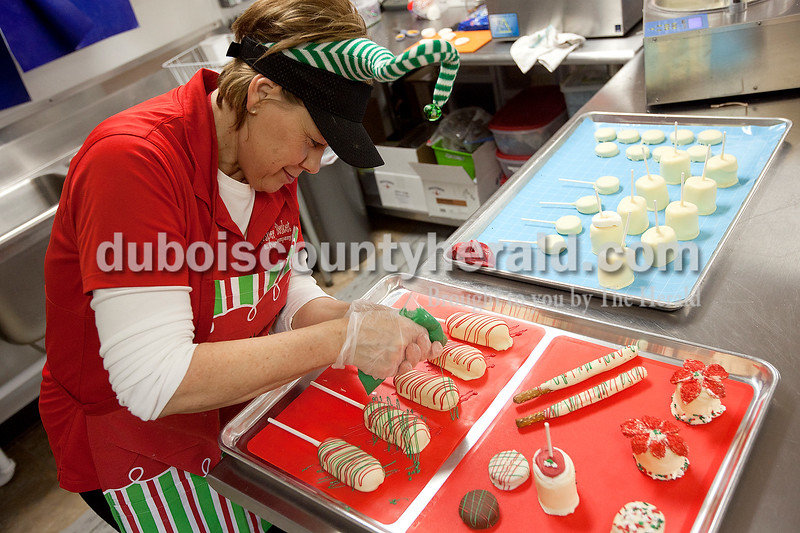Dave Weatherwax/The Herald<br /> Becky Troesch of Ferdinand decorated Twinkies after they had been dipped into white chocolate on Monday at the Jasper Gift Basket and Popcorn Company in Jasper.