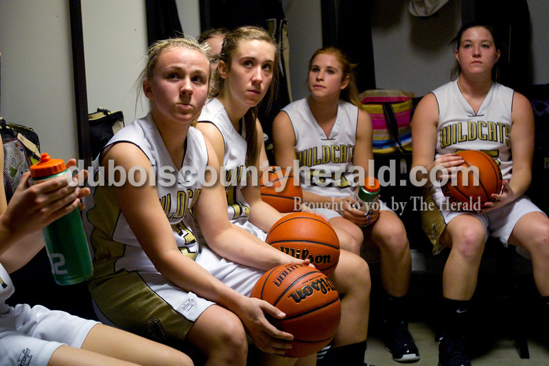 Olivia Corya/The Herald<br /> Jasper's Nicolette Eckert, left, Allyson Lents, Tori Sermersheim and Brooke Lueken listened to their coach discuss strategy before Saturday night's game against Southridge at Cabby O'Neill Gymnasium. The Wildcats defeated the Raiders 44-28.