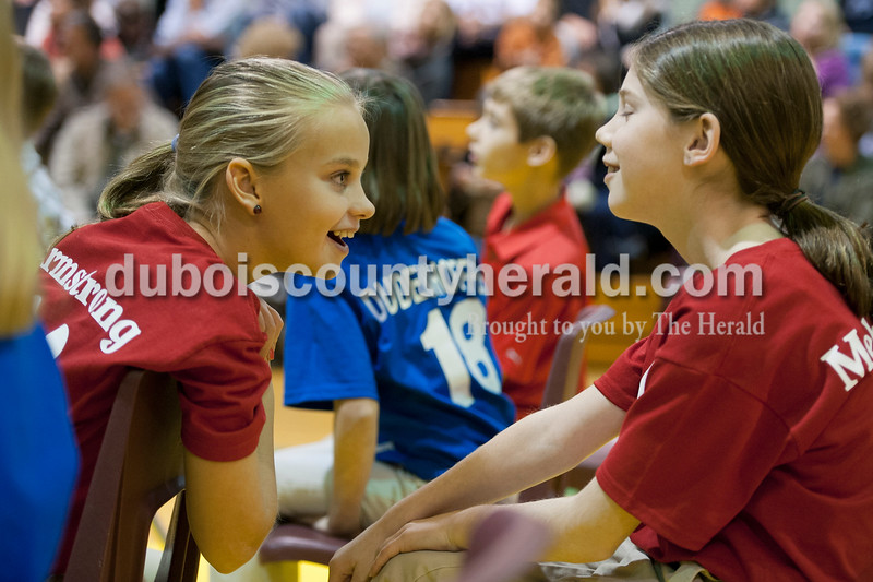 Olivia Corya/The Herald<br /> Precious Blood School student Abbey Armstrong, left, whispered to fellow fifth grader and spell bowl teammate Breann Mehringer during the Indiana Academic Spell Bowl Elementary Division at Ireland Elementary School on Thursday night. Precious Blood placed second in Class 4.