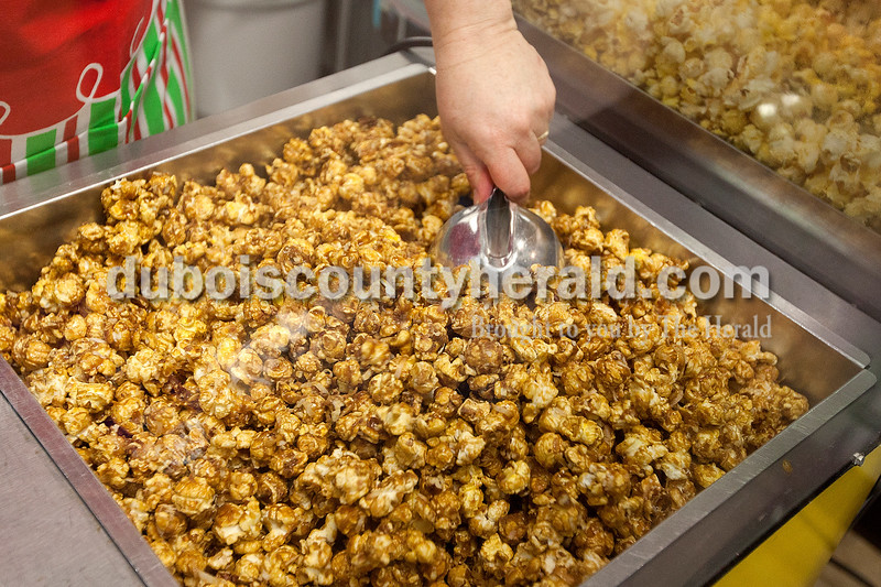 Dave Weatherwax/The Herald<br /> Jackie Seifert of Jasper waited for the German Chocolate Crunch carmel corn to cool before she could drizzle chocolate on it on Monday at the Jasper Gift Basket and Popcorn Company.  The business offers 80 flavors of popcorn.