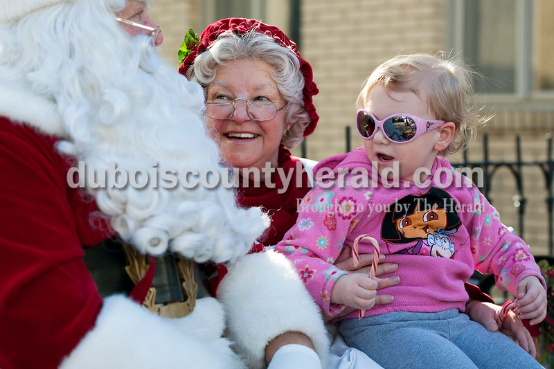 "Olivia Corya/The Herald<br /> Lilly Arvin of Jasper, 2, told Santa she just wanted ""presents"" for Christmas as she sat on Mrs. Claus's lap during the 27th annual Huntingburg Christmas Stroll in the downtown historic district on an unusually warm November Saturday. Sponsored by the Huntingburg Merchants Association, the event also included carolers, shopping, and free gift wrapping."