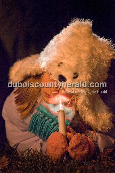 Rachel Mummey/The Herald<br /> Katey Schaefer of Ferdinand, 7, nuzzled her cheek against her candle while watching the opening ceremonies of the 15th annual Christkindlmarkt at the Monastery of Immaculate Conception in Ferdinand Friday.
