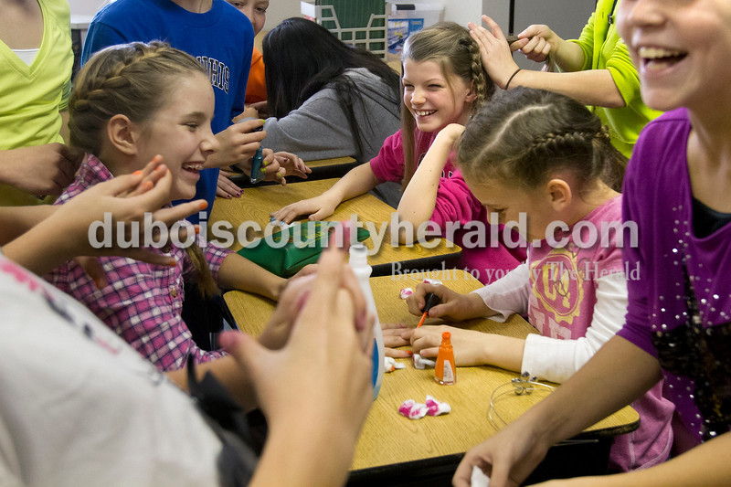 Olivia Corya/The Herald<br /> Keely Magee, center top, had her hair braided by Claire Knies while Olivia Biggs painted Kennedy Begle's nails and Isabelle Blazey, far right, laughed at Ireland Elementary School on Friday. Last month the school received a state accountability grade of A, and to reward the students for their hard work the faculty planned a day full of fun and games. After watching their teachers dance in a flash mob, students chose between several special activities including face painting, bingo, and card games to celebrate. All the girls pictured are in fifth grade.