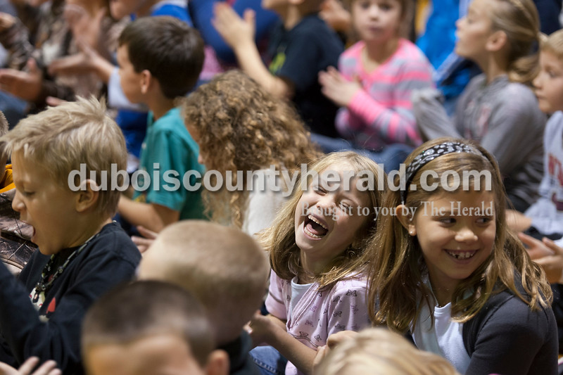 Olivia Corya/The Herald<br /> Ireland Elementary School second grader Alexis Byrd, center, sitting next to her classmate Anna Underwood, applauded for her school's academic success during a surprise assembly in the gymnasium on Friday. Last month the school received a state accountability grade of A, and to reward the students for their hard work the faculty planned a day full of fun and games. After watching their teachers dance in a flash mob, students chose between several special activities including face painting, hair braiding, bingo, and card games to celebrate.