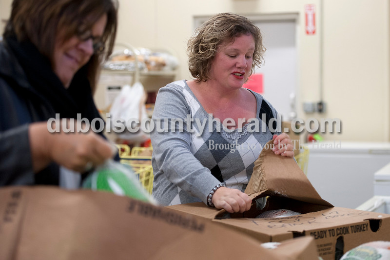 Olivia Corya/The Herald<br /> Community Food Bank manager Amanda Drew of Jasper unpacked turkeys that were purchased with money donated during the annual turkey drive for families in need in Jasper on Wednesday. So far this year the food bank has received 59 turkeys and a little short of $1,000 in donations, which still puts them short of the 150 goal. This goal is higher than last year's turkey total, which was about 130. Helping Drew with the birds is her friend from her full-time job Beth Otto of Glendale, who was just lending a hand for the day.