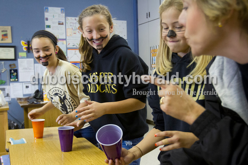 Olivia Corya/The Herald<br /> Parent volunteer Jeana Harpenau of Jasper taught fifth graders Reagan Egbert, left, Meredith Hilgefort and Halee Harpenau a cup stacking game at Ireland Elementary School on Friday. Last month the school received a state accountability grade of A, and to reward the students for their hard work the faculty planned a day full of fun and games. After watching their teachers dance in a flash mob, students chose between several special activities including face painting, hair braiding, bingo, and card games to celebrate. Jeana is Halee's mother.