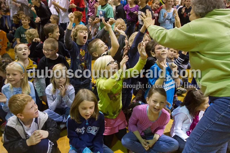 Olivia Corya/The Herald<br /> Ireland Elementary School second grader Taryn Schmitt jumped up to receive a high five from teacher Darlene Ziegler during a surprise assembly in the gymnasium on Friday. Last month the school received a state accountability grade of A, and to reward the students for their hard work the faculty planned a day full of fun and games.