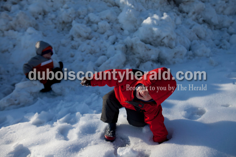 Matthew Busch/The Herald<br /> Grant Meiring, 2, fell in a snow pile outside of St. Joseph Catholic Church in Jasper as he played with his brother Xavier, 5, and grandmother, Yvonne Mullen of Jasper, not pictured, on Thursday.