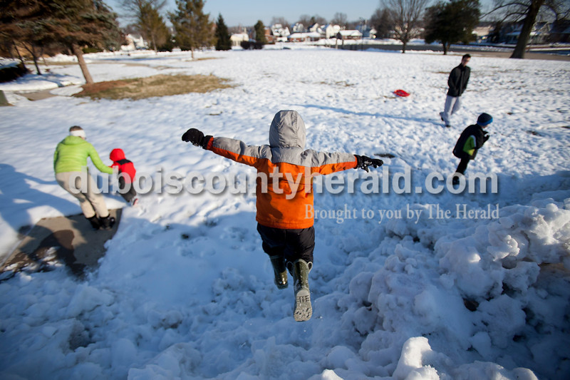 Matthew Busch/The Herald<br /> Xavier Meiring, 5, center, leapt from a snow bank outside of St. Joseph's Catholic Church in Jasper on Thursday. Xavier was playing outside with his grandmother Yvonne Mullen, left, and brother Grant Meiring, 2, second left as she took care of them during the day on Thursday before their father picked them up. Mullen takes care of her grandsons on Thursdays and usually takes them to Sarah's Playground by Ruxer Field in Jasper. Also playing in the snow was Matthew Cyrill, top right, and his neighbor Spencer Baugh, both of Jasper.