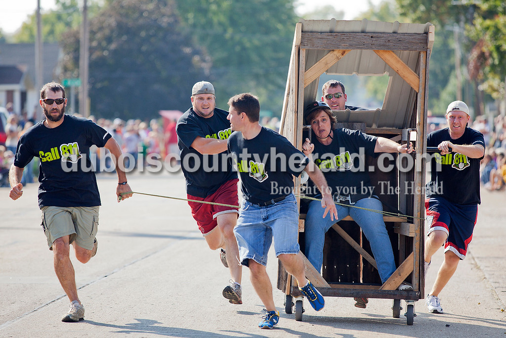 Kim Howe of Jasper hung on while seated in her team's entry in the outhouse race at the Herbstfest as Ryan King, left, Luke Rasche, Tony Traylor, Brad Coomer and Jonathan Ruppe, all of Huntingburg, raced down First Street in Huntingburg on Saturday. The team, made up of Huntingburg utility workers, called itself Nap's Crew. Howe said she didn't have a choice on whether she wanted to participate because she is the only woman at their office and teams required one female. Rachel Mummey/The Herald