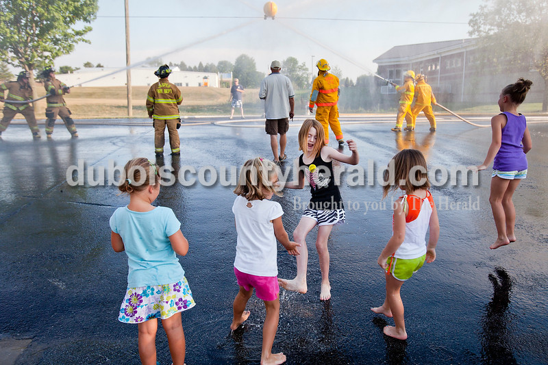 Kiersten Hubbs, 5, left, Raven Meyer, 5, Ava Hamilton, 8, Allison Wahl, 5, and her sister Amy, 8, all of Ferdinand, played in the water alongside the waterball competition during the Heimatfest celebration in Ferdinand on Friday evening. Rachel Mummey/The Herald