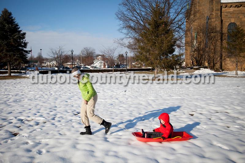 Matthew Busch/The Herald<br /> Yvonne Mullen of Jasper pulled her grandson Grant Meiring, 2, behind her on a sled outside of St. Joseph Catholic Church in Jasper on Thursday.
