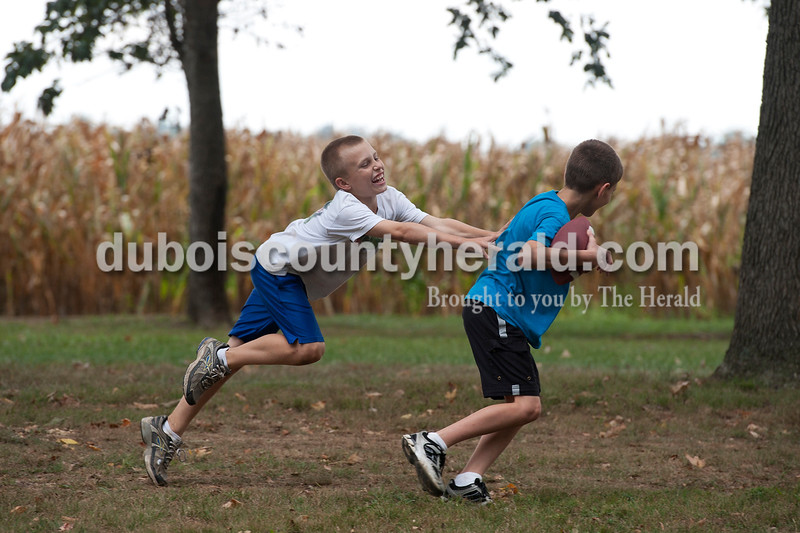 Luke Harder of Dubois, 10, chased his friend Ethan Breitwieser of Jasper, 10, while they played with a football together during the Dubois Septemberfest at Dubois Community Park on Saturday.  Olivia Corya/The Herald
