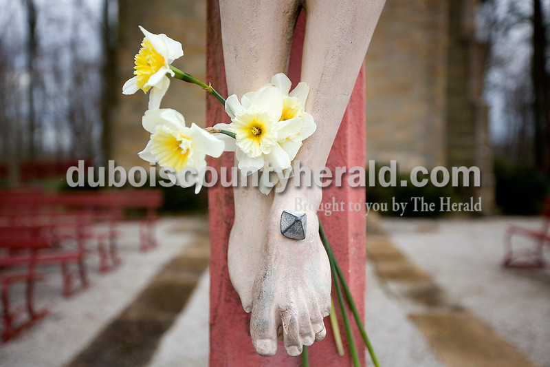 Flowers were left at the feet of the Christ crucifixion statue in front of the Monte Cassino shrine in St. Meinrad. Dave Weatherwax/The Herald