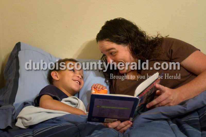 DreShawn Boyd, 5, left, listened to his mother, Crystal Salmon, read him a bedtime story at their Jasper home on Thursday. Every Thursday, DreShawn picks out a new book at school and they read the book together that night.  Olivia Corya/The Herald