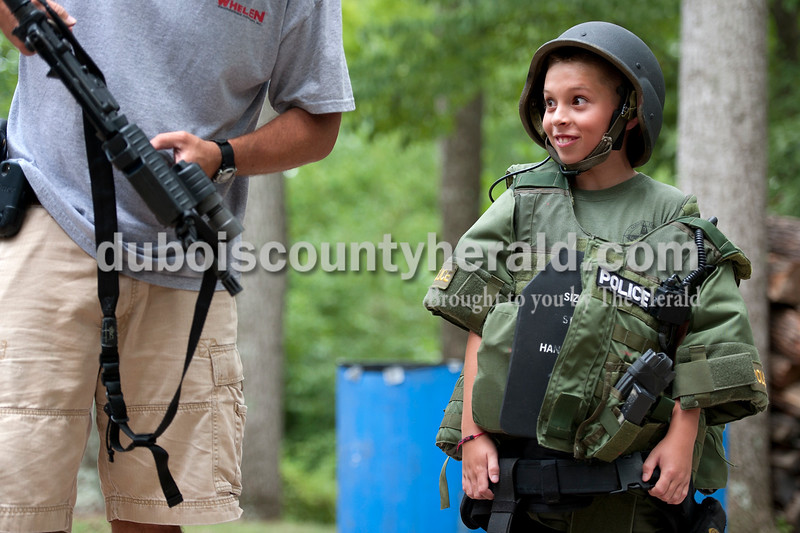 Kaleb Phelps of Dale, 10, modeled Special Weapons and Tactics gear while eyeing a gun held by Jasper Assistant Police Chief Nathan Schmitt during Fraternal Order of Police Lodge 138's annual Kids Camp in the woods near the Jasper lodge Friday. The two-night camp included explosion demonstrations and the opportunity for children to hold a fire hose as it blasted water. Olivia Corya/The Herald