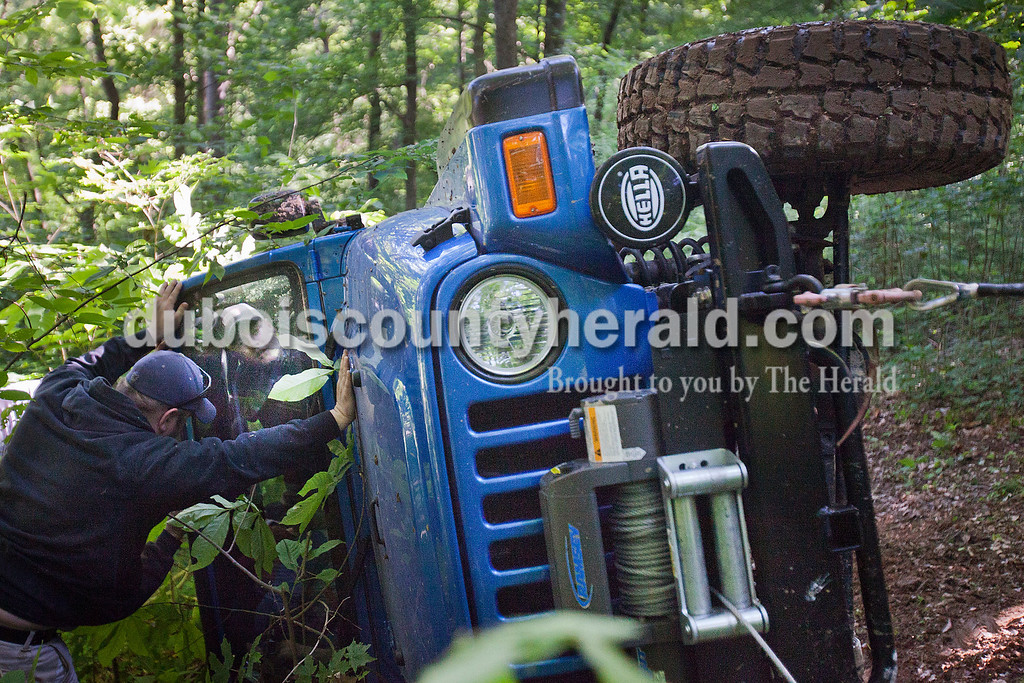 While en route from one trail to another, Jamin Hochgesang's 2003 Jeep Wrangler hit a soft patch and turned over onto its side May 11. Jayson Soliday of Fishers helped push as winches pulled the vehicle back upright.  Rachel Mummey/The Herald