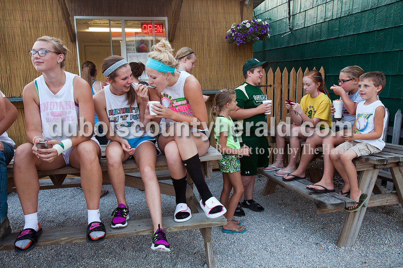 Kylie Blessinger, 17, third from left, took a taste of slushie from Tori Lange, 16, second from left, while sitting with Mackenzie Weyer, 17, left, all of Ferdinand, as they spent a warm summer evening hanging out at the Ferdinand Slushie Stand after finishing league sports night in Ferdinand  on June 27. A younger group of kids including, Karli Kitten, 7, her cousin, Sara Kitten, 9, Nolan Gentry, 12, Kay Leigh Wahl, 12, Maggie Brown, 11, and Karli's brother, Jake Kitten, 5, all of Ferdinand, showed up to enjoy a slushie too.<br />  Rachel Mummey/The Herald