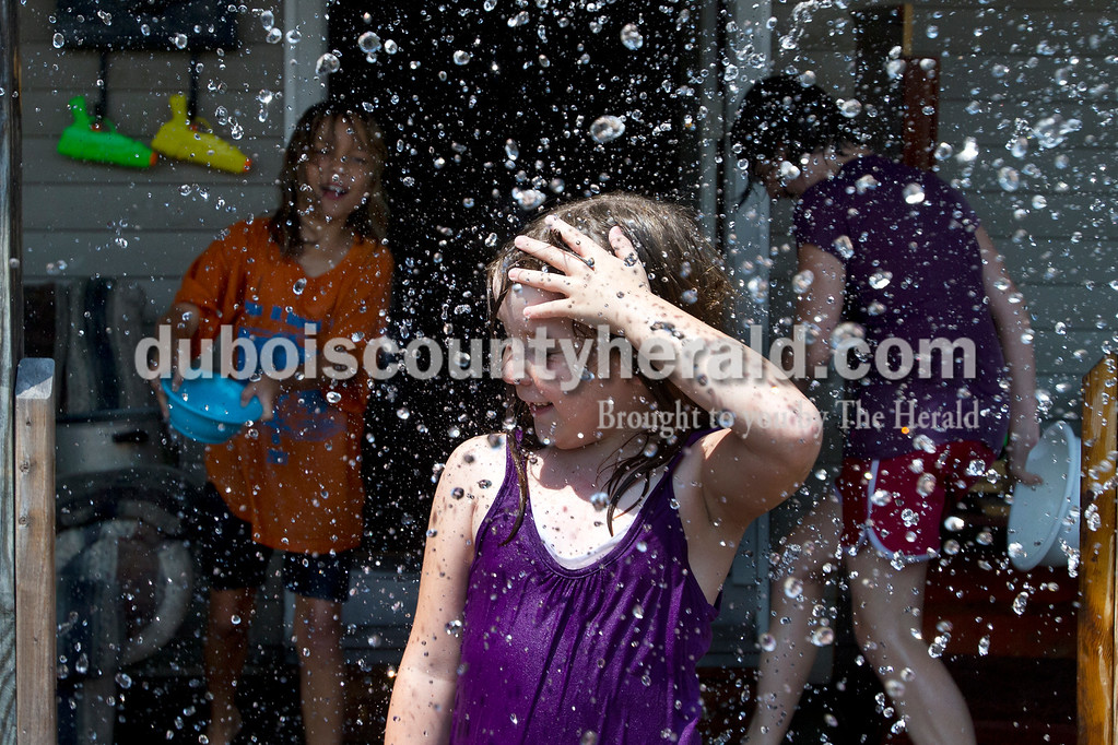 Alisha Howard of Jasper, 8, welcomed a deluge of water thrown by her stepsister Tarzana Sadler of Haysville, 8, outside Alisha's Jasper home Monday. The girls filled pots, pans, and squirt guns with ice water to cool down in the midday sun. Olivia Corya/The Herald