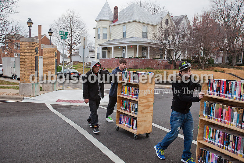 Rachel Mummey/The Herald<br /> Leonel Hernandez of Huntingburg, left, Gary Hires of Jasper, middle, and Brandon Taylor of Jasper, right, carted books across Main Street from the Jasper Public Library to be packed into storage units on Monday. The men were part of a work crew from Community Corrections who were completing community service hours by moving some of the library's 118,000 collection items. The Jasper Public Library is closed through Dec. 26 to allow the staff to install new shelving, tables and computer workstations, rearrange book sections, and add a new self-checkout station.