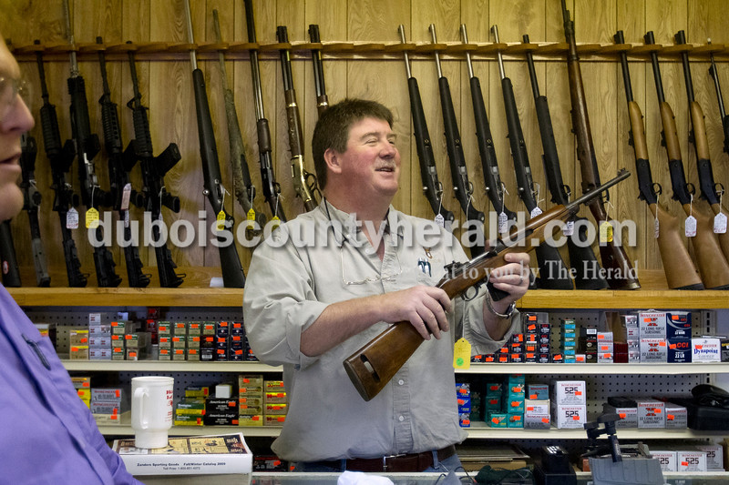 Olivia Corya/The Herald<br /> Jeff's Bait & Guns owner Jeff Miley of Jasper laughed with another customer while showing a rifle to Andrew Bennington of Washington at the shop in Jasper on Wednesday. Local gun vendors have enjoyed a recent boost in sales. They attribute the uptick partly to the reelection of President Obama, whom many customers expect to tighten gun control legislation. This trend likely owes more to current gun owners purchasing additional firearms than it does to an increase in first time buyers; according to the General Social Survey conducted by the University of Chicago, the percentage of gun owning Americans has steadily declined for three decades.
