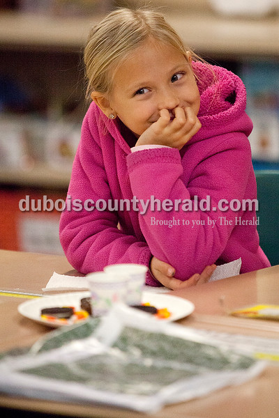 Rachel Mummey/The Herald<br /> First-grader Clair Leathers giggled while listening to One Is a Feast for Mouse during the Dubois County Family Literacy Night at Huntingburg Elementary School on Tuesday.
